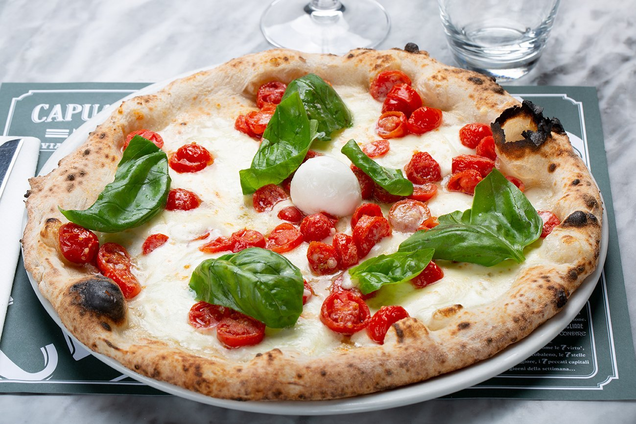 Pizza Gran Bufala di Capuano's, con mozzarella di bufala D.O.P., pomodorini datterini, grana, basilico, olio DOP della penisola sorrentina appena uscita dal forno